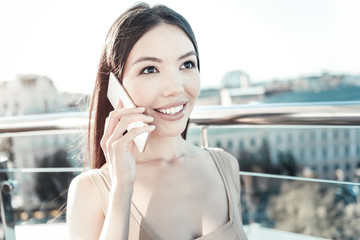 Best connection. Cute talkative smart woman standing on the rooftop smiling and holding cellphone near head.