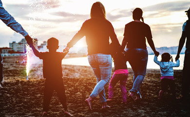 Family friends holding eache others hands around fireworks at sunset on the beach