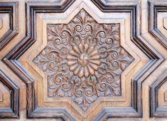Eight-pointed star, closeup of a carved wooden door in a church of Seville, Spain