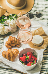 French style romantic summer picnic setting. Flat-lay of glasses with rose wine, fresh strawberries, croissants, brie cheese on wooden board, hat, sunglasses, peony flowers. Outdoor gathering concept