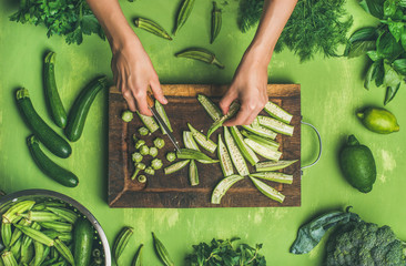 Tuinposter Koken Healthy vegan cooking ingredients. Flay-lay of woman hands cutting green vegetables and greens on board over wooden green background, top view. Clean eating, vegetarian, detox, dieting food concept