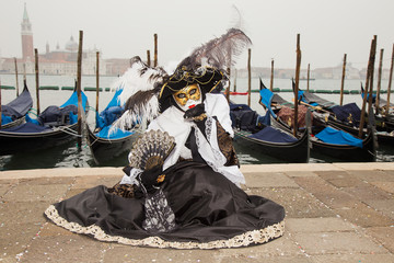 Female Venetian Mask in black and white elegant costume with venetian gondolas - Venice Carnival