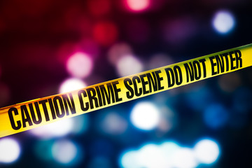 high contrast image of Crime scene tape with red and blue lights on the background