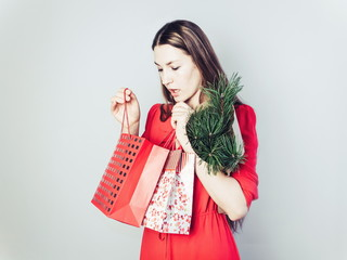 Young, sweet and happy woman in a red dress joyfully viewing wonderful gifts in bright packages