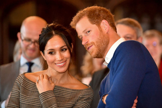 Britain's Prince Harry whispers to Meghan Markle as they watch a dance performance by Jukebox Collective in the banqueting hall during a visit to Cardiff Castle in Cardiff