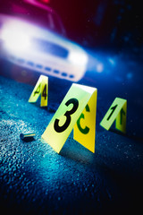 Fototapeta police car at a crime scene with evidence markers, high contrast image