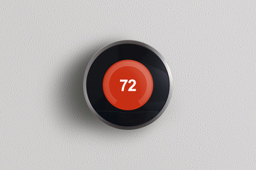 A simplistic photo of a round, modern, programmable digital thermostat in heating mode, on a clean white wall.