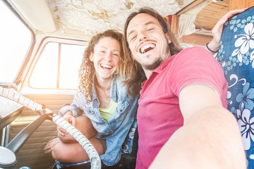 Happy couple inside minivan for a road trip - Adult people taking selfie on summer vacation traveling around the world - Travel, technology, love and van lifestyle concept - Focus on man face