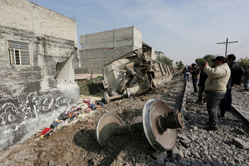 Man takes pictures of the car of a cargo train that ran off the tracks knocking a home in the municipality of Ecatepec