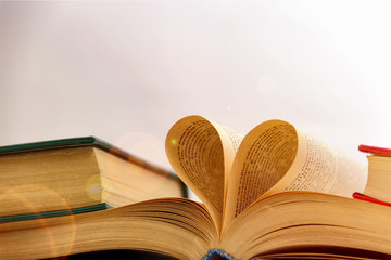 An open book with a heart from the pages, a love of reading and science.