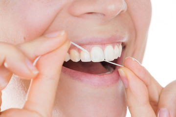 Young girl with a healthy smile using dental floss