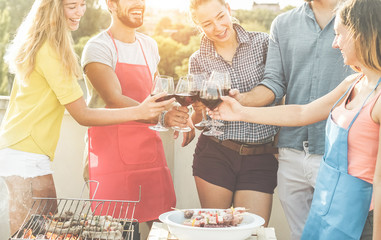 Happy friends cheering with red wine at barbecue dinner party - Young people doing bbq meal outdoor with sunset in background - Food, fun, youth lifestyle and friendship concept