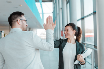 Two business people high-five. Job well done.