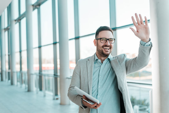 Handsome smiling bearded businessman is waving.
