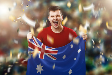 Australian fan, a fan of a man holding the national flag of Australia in his hands. Soccer fan in the stadium. Mixed media