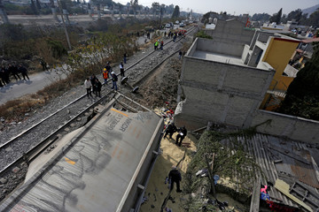 Security forces and railroad workers stand next to the car of a cargo train that ran off the tracks knocking a home in the municipality of Ecatepec