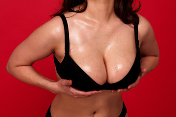 Voluptuous busty woman posing on a red background