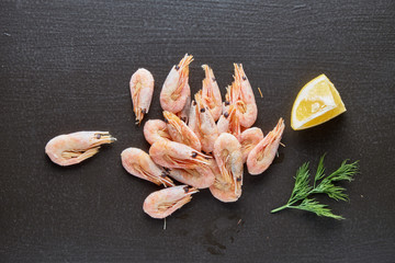 Delicious boiled shrimps with lemon and greens on a black background