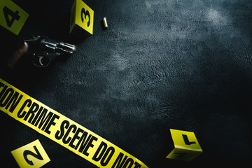 Crime scene concept with a gun and evidence markers , high contrast image