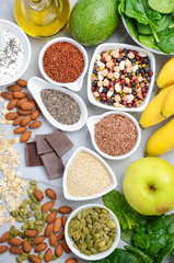 Healthy food nutrition dieting concept. Banana, chocolate, spinach, avocado, apple, quinoa, chia, flax seeds, yogurt, almond, beans, oat, pumpkin seeds, olive oil. Top view, flat lay.