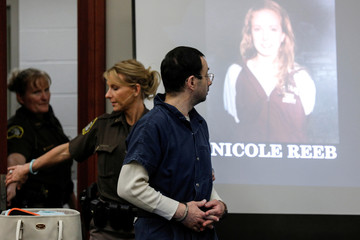 Larry Nassar, a former team USA Gymnastics doctor who pleaded guilty in November 2017 to sexual assault charges, passes a picture of victim and former gymnast Nicole Reeb during his sentencing hearing in Lansing