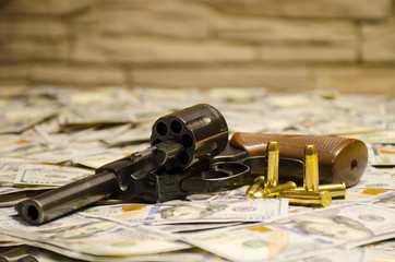 The weapon with bullets laid down on blurred dollars