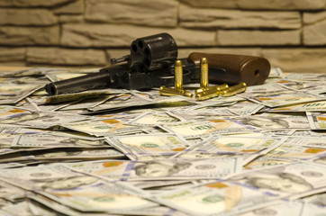 The weapon with blurred bullets in background laid down on blurred dollars