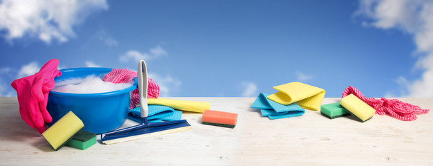 Spring cleaning banner, blue plastic bowl with soap foam, pink rubber gloves, rags, sponges and window wiper on white wooden planks against a blue sky with clouds, panoramic format, copy space