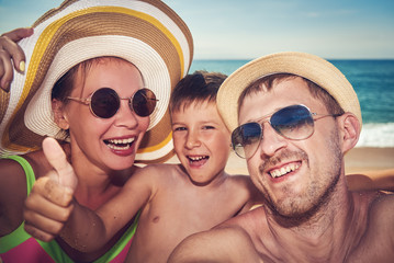 Family is taking a selfie photo while having a rest on the beach.