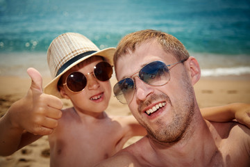 Father is taking a selfie photo with son while having a rest on the beach.