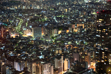 Small houses are in the Nishi-Shinjuku. It is a skyscraper business district in Shinjuku. Aerial view at night time. From the side is Tower La Tour apartment building. Tokyo, Japan