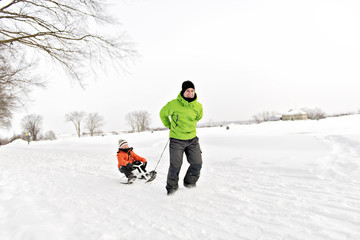 Father drag his boy in sled