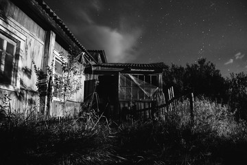 Old ramshackle house. The beautiful night scenery. Slow shutter speed. Spectacular clear starry sky. Scenic view. Green grass