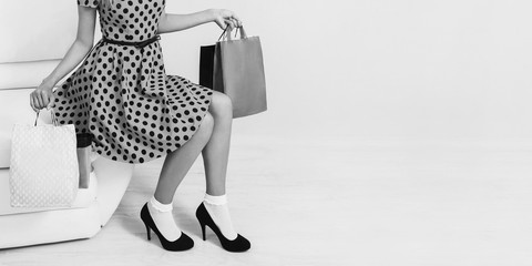 Girl in blue dress and black shoes with shopping bags on a white background. Black Friday