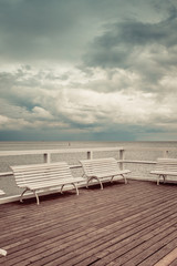 Wooden pier with white benches on sea