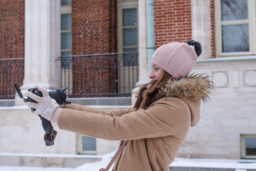 Young woman tourist takes off on the camera in winter
