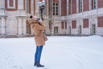 Young female tourist takes photos of architecture