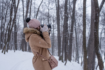 Young woman tourist takes photos of nature in winter