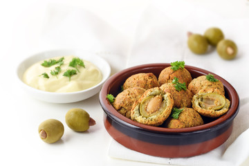 baked olive balls in parmesan dough coat with a creamy garlic sauce, spanish tapas appetizer in a typical ceramic bowl on a white napkin, copy space