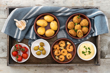 party  appetizers , spanish tapas , such as baked olives, prawn shrimps, potatoes, tomato and garlic dip on a rustic wooden tray with a blue gray kitchen towel, flat top view from above