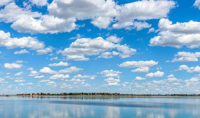 Spring Clouds - White spring clouds, on blue sky, rolling pass a city lake. Marston Lake, Denver-Lakewood, Colorado, USA.