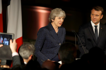 Britain's Prime Minister Theresa May and France's President Emmanuel Macron are welcomed by the other diners at an official dinner at the Victoria & Albert Museum in central London