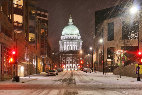 Beautiful night cityscape. Madison, the capitol of Wisconsin downtown street view with parked cars and Wisconsin state capitol building glowing in the snowy night. Wisconsin state, Midwest USA.