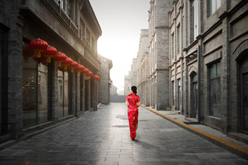 Asian young woman in old traditional Chinese dresses in Hutong village in Beijing, China.