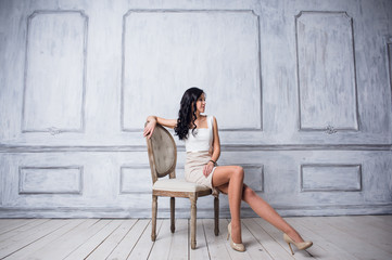 Fashion shot of young beautiful woman in white short dress sitting in antique chair