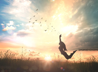 International migrants day concept: Silhouette of a woman jumping and broken chains at sunset meadow with her hands raised.