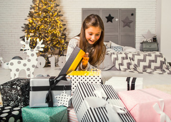 little girl at christmas opens gifts