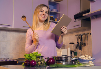 Beautiful cute, young woman , cooking and holding tablet in her hands, looking to find recipe on internet