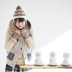 テーブルの上に並ぶ雪だるまを見る女性