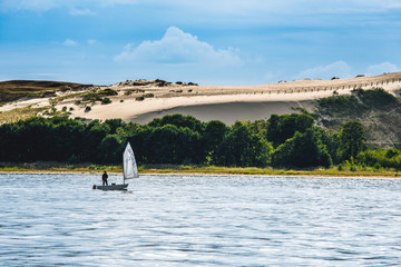 Parnidis dunes and small yacht in a curonian lagoon. Nida city, Lithuania